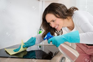 Young Woman Smiling While Cleaning Induction Hob On Countertop At Home